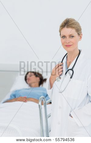 Portrait of a smiling doctor with patient in background at hospital