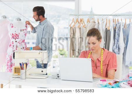 Young woman using laptop with male fashion designer working in background at the studio