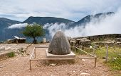 picture of oracle  - The view on Omphalos or Baetylus the famous religious stone artifact that was the center of the Universe for ancient greeks Delphi Greece - JPG