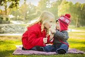 stock photo of lollipops  - Little Girl with Her Baby Brother Wearing Winter Coats and Hats Sharing a Lollipop Outdoors at the Park - JPG