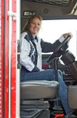 picture of big-rig  - A woman truck driver looking across the passenger seat - JPG