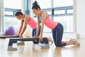 picture of step aerobics  - Side view of two fit women performing step aerobics exercise in gym - JPG