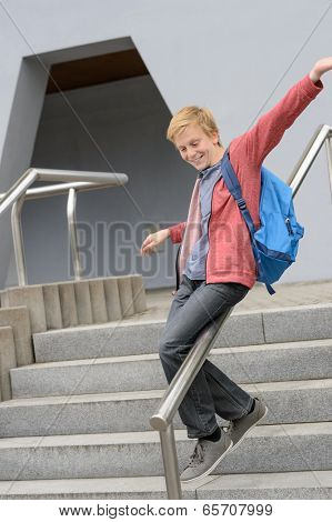 Excited teenage student sliding down handrail on school stairway