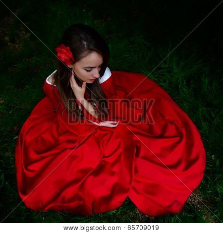 beautiful woman with red cloak  in the woods in spring
