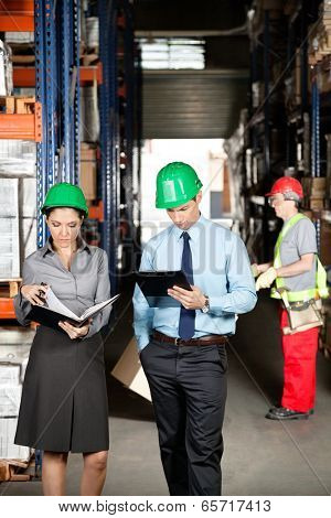 Female supervisor with colleague working at warehouse with foreman unloading cardboard boxes