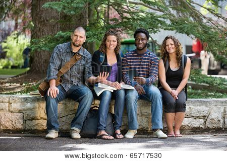 Full length portrait of multiethnic students sitting on parapet at university campus