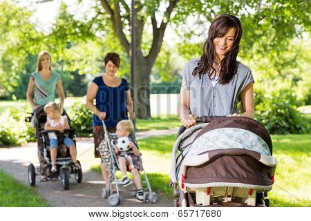 Young mother looking at baby in stroller at park with friends and children in background