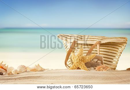Summer concept with sandy beach, shells and bag