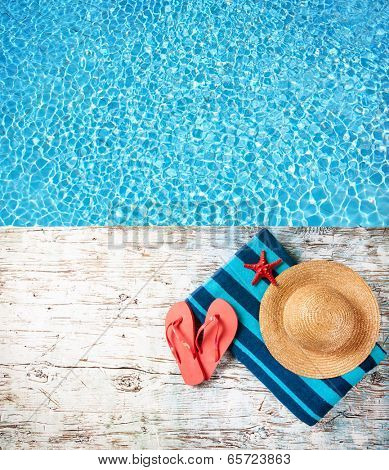 Concept of summer accessories on wood with blue water as background