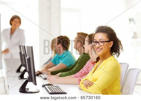 education, technology and school concept - smiling male student with classmates in computer class with teacher