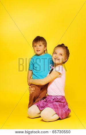 Girl cuddle standing child while sitting on floor