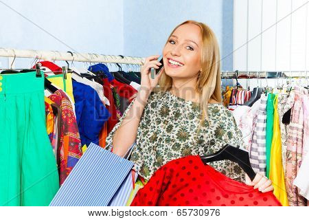 Young woman talking on mobile phone in the shop