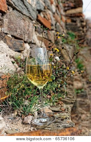Full glass of Riesling wine on slate rock, Moselle winemaking region, Germany