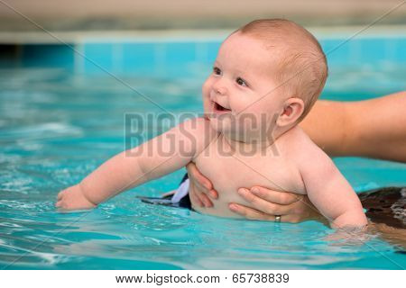 Happy Infant Baby Boy Enjoying His First Swim In Pool