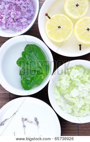 Aromatherapy treatment bowls with flowers and perfumed water on bamboo mat background