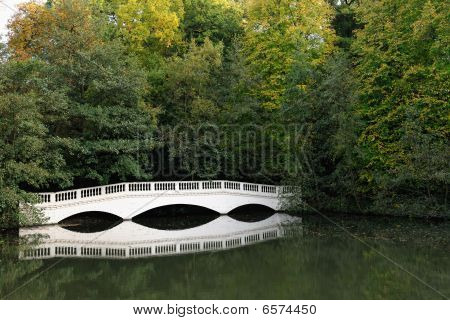 Sham White Wooden Bridge At The End Of A Lake, Surrounded By Autumn Trees
