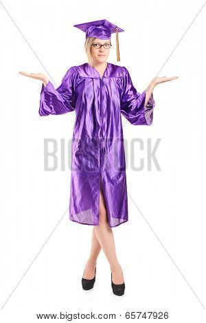 Full length portrait of a woman in graduation gown gesturing uncertainty isolated on white background