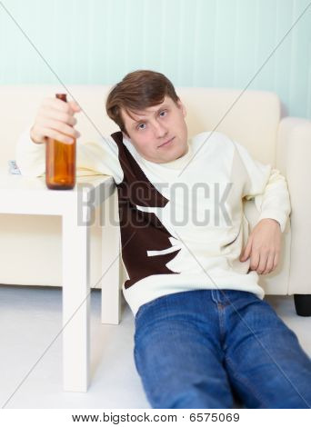 Drunken Man Sits On Floor With Beer Bottle