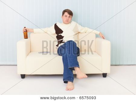 Man Sits On Sofa With Beer Bottle In A Hand