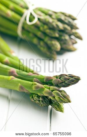 green asparagus on white wooden table