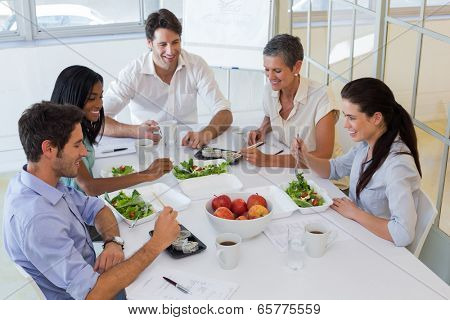 Workers eating fruit and salad together for lunch in the office