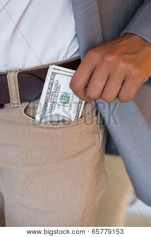 Dodgy businessman pocketing wad of dollars in his office
