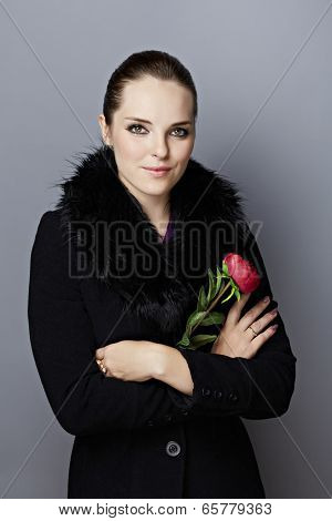 Portrait of a  young woman, with long brunette hair pulled back, on gray studio background, wearing black wool coat with faux fur collar