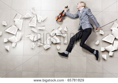 Funny image of running businessman with violin in hand