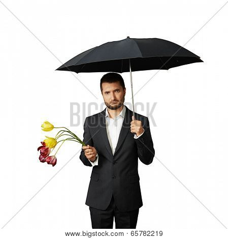 sad man with faded flowers standing under umbrella. isolated on white background