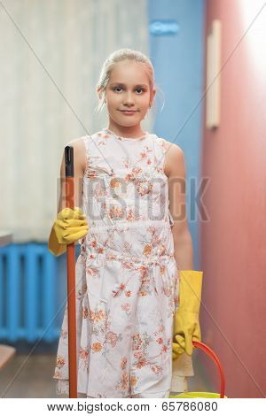 Cute Teenage Blond Girl Holding Cleaning Tools In The Kitchen