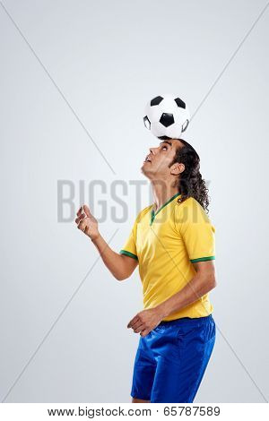 football player ballancing soccer ball on head in display of skill