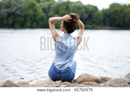 Sad woman sitting on rocks on the river arms folded on her lap and staring into the distance