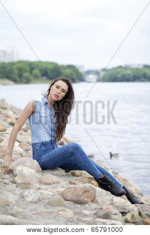 Sad woman sitting on rocks on the river