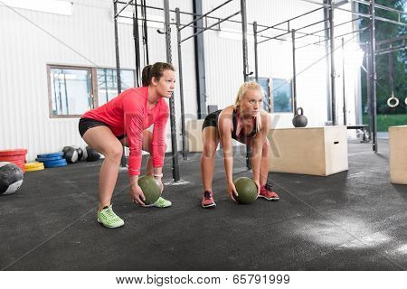 Two women lifts crossfit slam balls