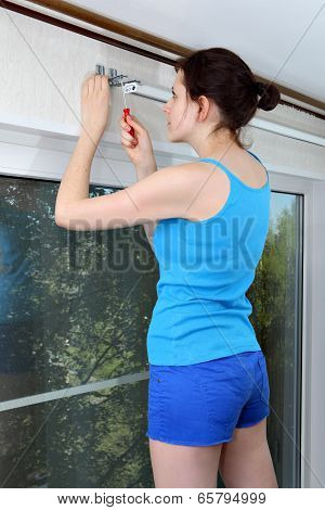 Girl Mounts Vertical Blinds On Wall,  Tighten Screw Red Screwdriver