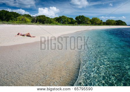 Young woman relaxing on the tropical beach. Bali, Indonesia