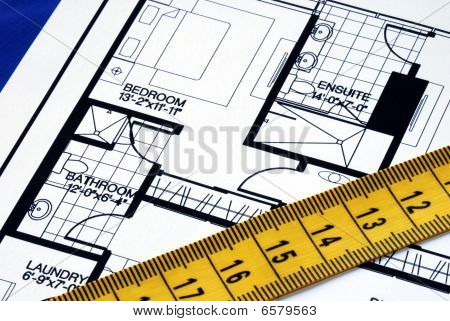 Measure the floorplan with a  measuring tape isolated on blue