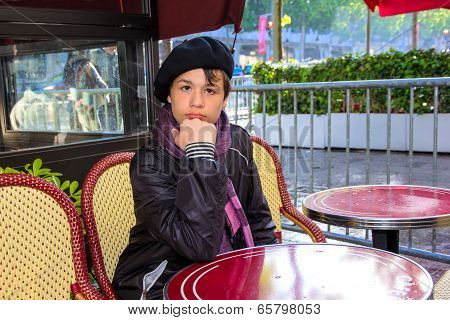 Teenager Sitting At A Table Cafe On The Champs Elysees, Paris, France