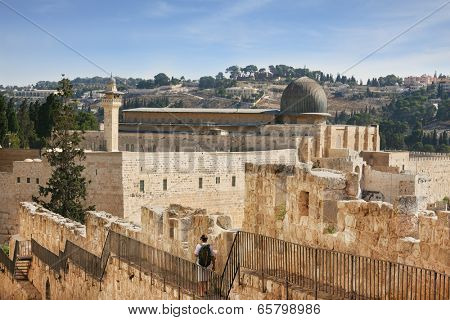 Along the walls of Jerusalem strolls thoughtful woman pilgrim with a backpack. In the distance you can see the gray dome of the Al-Aqsa Mosque and the Muslim minaret