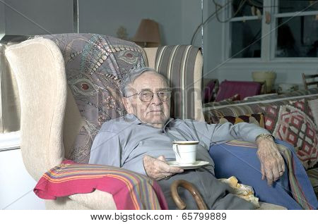 Senior Man Sitting On Couch With Cup