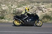foto of crotch-rocket  - Speeding motorcycle racing around a corner on a country back road - JPG