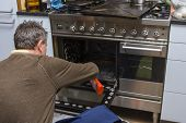 pic of kneeling  - A man kneeling on the kitchen floor and cleaning the inside of an oven - JPG