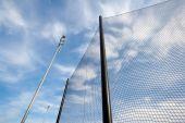 Image of backstop net and lights at baseball field.