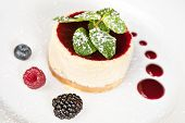 picture of cheesecake  - Cheesecake with bilberry raspberry blackberry powdered sugar and mint twig - JPG