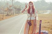 foto of hippies  - Hippie girl with peace signs in golden field - JPG