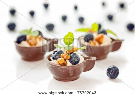Three Blueberry And Mascarpone Dessert In Chocolate Cups, Garnish With Caramelized Walnuts And Mint,
