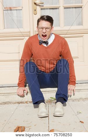 Angry  Handsome Man With Glasses And Sweater Sitting On Steps In Front Of House And Posing