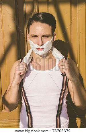 Closeup Of Handsome Man With Shaving Foam On His Face And Towel Around His Neck Posing
