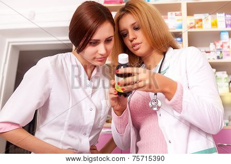 Two Pharmacist Woman Looking At Bottle
