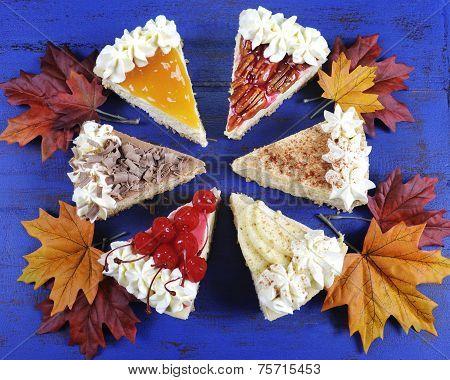 Thanksgiving Apple, Pecan, Cherry, Caramel, Pumpkin Spice And Chocolate Cream Cheesecake Pie On Dark